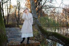 Mulher bonita em um chapéu do revestimento e em um vestido branco para uma caminhada em um parque ou em uma floresta do outono Foto de Stock
