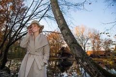 Mulher bonita em um chapéu do revestimento e em um vestido branco para uma caminhada em um parque ou em uma floresta do outono Fotografia de Stock