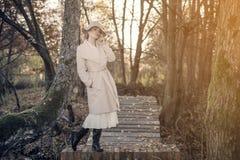 Mulher bonita em um chapéu do revestimento e em um vestido branco para uma caminhada em um parque ou em uma floresta do outono Fotos de Stock Royalty Free