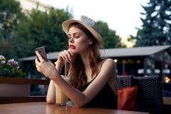 A mulher bonita em um chapéu guarda um telefone que senta-se em um café no terraço foto de stock royalty free