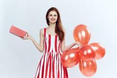 A mulher bonita em um fundo branco guarda uma caixa, presentes, retrato, feriado, balões, vermelhos Imagens de Stock
