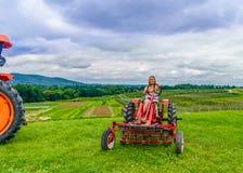 Mulher bonita em um trator agrícola vermelho, campo verde, paisagem do prado com grama do norte do estado New York foto de stock royalty free