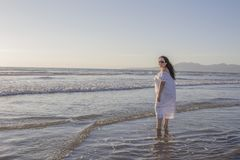 Mulher bonita em um vestido branco e em óculos de sol que aprecia a água do mar imagens de stock royalty free