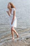 Mulher bonita em um vestido branco na costa Fotos de Stock