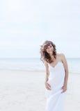 Mulher bonita em um vestido branco na menina feliz da costa do oceano na praia, o cabelo de vibração do vento Imagem de Stock Royalty Free