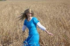 Mulher bonita em um vestido longo azul no campo de cereais maduros Foto de Stock Royalty Free