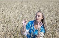 Mulher bonita em um vestido longo azul no campo de cereais maduros Fotografia de Stock Royalty Free