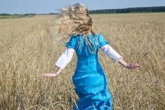 Mulher bonita em um vestido longo azul no campo de cereais maduros Fotos de Stock Royalty Free