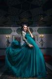 Mulher bonita em um vestido longo verde em um fundo de ricamente Imagens de Stock