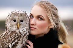 Mulher bonita em um vestido preto com uma coruja em seu braço Louro com cabelo longo na natureza que guarda uma coruja Menina del Imagem de Stock