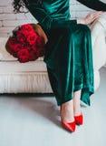 Mulher bonita em um vestido verde e em umas sapatas vermelhas com rosas vermelhas Imagens de Stock Royalty Free