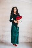 Mulher bonita em um vestido verde e em umas sapatas vermelhas com rosas vermelhas Fotos de Stock