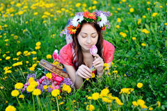 Mulher bonita em um vestido vermelho que encontra-se no prado com flores amarelas Fotografia de Stock