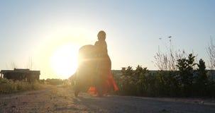Mulher bonita em um vestido vermelho que monta sua criança em um pram no por do sol no slo-mo filme