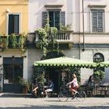 Mulher bonita em uma bicicleta em Milão na frente de um café durante um dia ensolarado imagem de stock