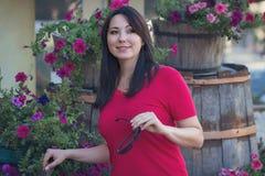Mulher bonita em uma blusa vermelha em uma cama de flor Fotos de Stock