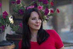 Mulher bonita em uma blusa vermelha em uma cama de flor Imagens de Stock Royalty Free