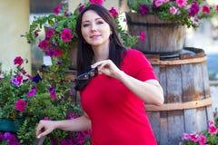 Mulher bonita em uma blusa vermelha em uma cama de flor Imagem de Stock