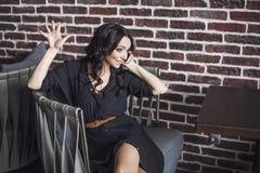 Mulher bonita em uma cadeira no restaurante com o telefone imagens de stock