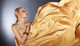 Mulher bonita em uma tela dourada de fluxo fotos de stock