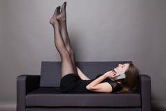 A mulher bonita encontra-se em um sofá e em um telefone de fala Imagens de Stock
