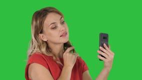 A mulher bonita enfeita-se usando seu telefone como um espelho em uma tela verde, chave do croma vídeos de arquivo