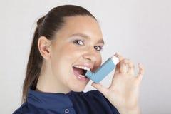 Mulher bonita, enfermeira, usando o inalador da asma Foto de Stock