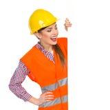 Mulher bonita entusiasmado no capacete de segurança que guarda a bandeira e a leitura Imagem de Stock
