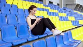 A mulher bonita escuta a música e surfar o Internet no smartphone em uma tribuna video estoque