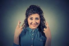 Mulher bonita esperançosa que cruza seus dedos Imagens de Stock Royalty Free