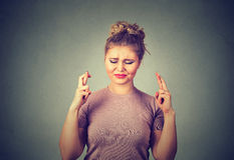 Mulher bonita esperançosa que cruza seus dedos, olhos fechados, esperando, pedindo melhor Fotos de Stock Royalty Free