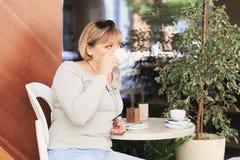 A mulher bonita está bebendo o café no café Fotos de Stock