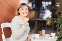 A mulher bonita está bebendo o café no café Foto de Stock