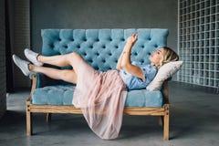A mulher bonita está encontrando-se no sofá com telefone imagem de stock