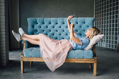 A mulher bonita está encontrando-se no sofá com telefone fotografia de stock royalty free