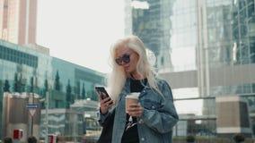 A mulher bonita está enviando uma mensagem de texto usando um app em seu smartphone ao andar no louro do modelo da rua filme