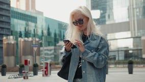 A mulher bonita está enviando uma mensagem de texto usando um app em seu smartphone ao andar no louro do modelo da rua video estoque