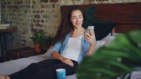 A mulher bonita está falando ao smartphone de utilização em linha do amigo que faz a chamada video, é feliz e entusiasmado Jovem  vídeos de arquivo