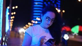A mulher bonita está na rua em um t-shirt branco e os vidros, fazem pagamentos em linha pelo cartão de crédito e pelo smartphone video estoque