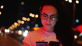 A mulher bonita está na rua em um t-shirt branco e os vidros, fazem pagamentos em linha pelo cartão de crédito e pelo smartphone filme
