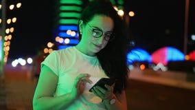 A mulher bonita está na rua em um t-shirt branco e os vidros, fazem pagamentos em linha pelo cartão de crédito e pelo smartphone vídeos de arquivo