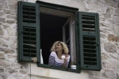 A mulher bonita está olhando na distância com a xícara de café em suas mãos Imagens de Stock