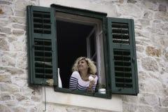 A mulher bonita está olhando na distância com a xícara de café em suas mãos Imagem de Stock Royalty Free