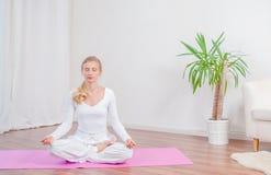 A mulher bonita está praticando a ioga em casa na esteira da ioga, menina que senta-se na pose de Lotus foto de stock