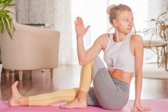 A mulher bonita está praticando a ioga, fazendo a pose de Ardha Matsyendrasana em casa fotografia de stock royalty free