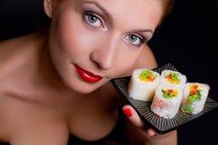 A mulher bonita está prendendo uma placa com alimento japonês Imagem de Stock