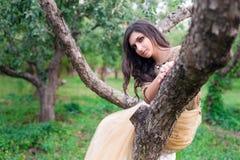A mulher bonita está sentando-se em uma árvore do verde do ramo Imagem de Stock