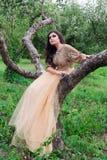 A mulher bonita está sentando-se em uma árvore do verde do ramo Imagens de Stock Royalty Free