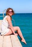 A mulher bonita está sentando-se no cais fotos de stock royalty free