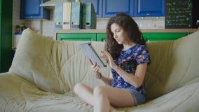 A mulher bonita está sentando-se no sofá e está usando-se o PC moderno da tabuleta à compra vídeos de arquivo